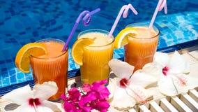 Trois verres de jus fraîchement serré par la piscine Images libres de droits