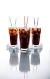 Trois verres de kola avec de la glace et des pailles sur un fond blanc Boissons non alcoolisées image stock