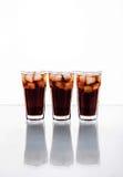Trois verres de kola et de glace sur un fond blanc Boissons non alcoolisées photographie stock libre de droits