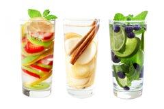 Trois verres de l'eau de detox de fruit d'isolement sur le blanc Photos stock
