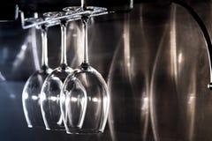 Trois verres de vin accrochant sur le support de barre ; Photo stock