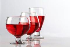 Trois verres de vin rouge sur le fond réfléchissant blanc Image libre de droits