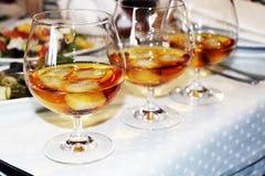 Trois verres de whiskey ou de cognac avec de la glace sur un dessus de table de serveur images libres de droits