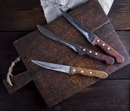 Trois vieux couteaux de cuisine sur une planche à découper en bois brune Photo libre de droits