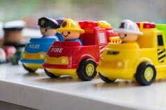 Trois voitures en plastique de jouet représentant les sapeurs-pompiers, le Département de Police et la récupération de place photo stock