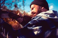 Trok de trekker van het jachtgeweer Stroper in Forest Hunter met jachtgeweerkanon op jacht Groot Spel stock afbeeldingen