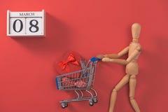 Trole da compra com a caixa de presente no fundo vermelho Loja do dia da mulher Foto de Stock Royalty Free