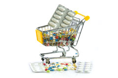 Trole da compra com os comprimidos isolados no fundo branco Foto de Stock