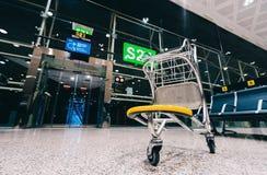 Trole do carro da bagagem na porta moderna do aeroporto foto de stock royalty free