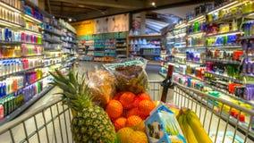 Trole no supermercado com produtos alimentares imagens de stock