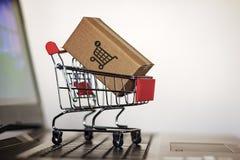 Troley с коробкой на клавиатуре компьютера Онлайн покупки, электронная коммерция и всемирная грузя концепция стоковая фотография rf
