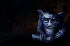 Troll. A dark bluish troll with teeth and glowing eyes sitting in the entrance of a cave.  Halloween concept Royalty Free Stock Photo