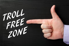 Troll Free Zone. Male hand pointing finger gesture at the phrase Troll Free Zone in white text on a blackboard Stock Image