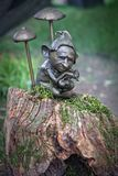 Troll. Sitting on a stump with mushrooms Royalty Free Stock Photography