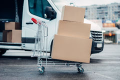 Trolley with boxes against truck, male logistic. Trolley with carton boxes against truck . Distribution business. Cargo delivery. Empty, clear containers. Mail Stock Photography