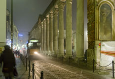 Trolley car in fog at night at San Lorenzo arcade, Milan Stock Photography