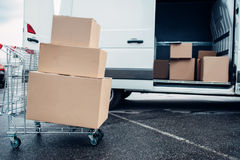 Trolley with cardboard boxes against mail van. Distribution business. Cargo delivery. Empty, clear containers. Logistic and post service Stock Photo