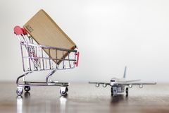 Trolley with carton and airplane. Worldwide Shopping and International shipping concept. Trolley with carton and airplane. Shopping and International shipping stock photos