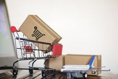 Trolley with cartons and airplane on computer. Online Shopping and International shipping concept royalty free stock photography