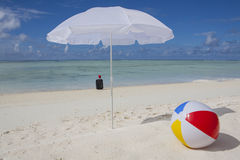 Trolley case at the beach. Trolley case with sun hat, beach ball and sunshade in summer Stock Photography