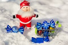 A trolley with Christmas toys candy on the background of Santa Claus. New Year greeting card. Merry Christmas and Happy New Year. A trolley with Christmas toys Stock Images