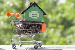 Trolley with coins and a house on a wooden table. A trolley with coins and a house on a wooden table on a blurred background of foliage. Sale, purchase, housing Stock Photography