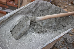 Trolley with Concrete and shovel, close up Stock Photos
