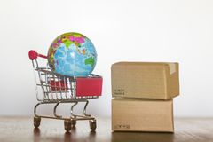 Trolley delivery cartons and earth globe. International shopping and global logistics concept.  stock photo