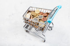 Trolley with euro coins on concrete board. Shopping trolley with euro coins on concrete board Stock Images