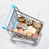 Trolley with euro coins on concrete plate Royalty Free Stock Photo