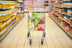 Trolley full of products. In supermarket Stock Photos