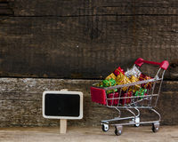 Trolley with gift boxes over wooden background Royalty Free Stock Image