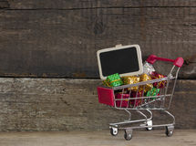 Trolley with gift boxes over wooden background Stock Photo