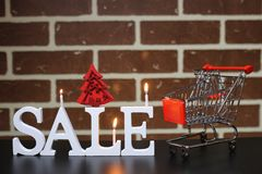 Trolley for products on a brick wall background New Year`s sale. Of shares Royalty Free Stock Image