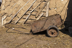 Trolley for removal of manure near a wooden shed Stock Photography