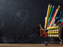 Trolley with school supplies on the background of a board Stock Photo