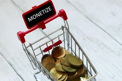 Trolley or shopping cart and gold coins with blackboard written with word monetize.Business and finance concept. Trolley or shopping cart and gold coins with stock photos
