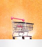 Trolley for shopping on a pedestal on a gold background with a glow. Best Buyer, Best Buy. Space for your text royalty free stock image