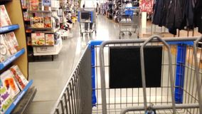 Trolley in store. Fast motion of woman pushing trolley inside Walmart store stock video footage