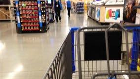 Trolley in store. Fast motion of woman pushing trolley inside Walmart store stock footage