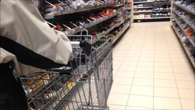 Trolley in store. Woman pushing trolley inside Canadian Tire store stock footage