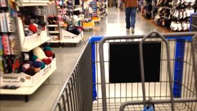 Trolley in store. Woman pushing trolley inside Canadian Tire store stock video