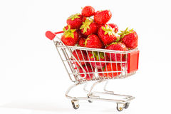 Trolley with strawberries. A lot of strawberries at miniature shopping cart Royalty Free Stock Image