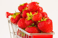 Trolley with strawberries. A lot of strawberries at miniature shopping cart Royalty Free Stock Photos