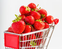 Trolley with strawberries. A lot of strawberries at miniature shopping cart Stock Image