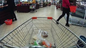 Trolley in a supermarket with goods go pro view stock footage