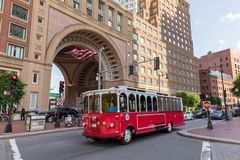 Trolley Tour bus in front of Boston Harbor Hotel. Outside of Boston Harbor Hotel in Boston Massachusetts, United States.  A public trolley crossing the street Royalty Free Stock Photography