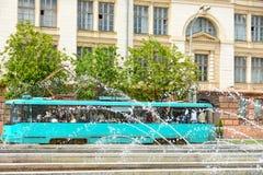 Trolleybus électrique de transport sur la route dans la ville pendant l'été sur un fond des jets de l'eau de la fontaine image libre de droits