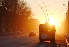Trolleybus locomotive   to the street. Street lighted up by the rays of a sunset sun Stock Photos
