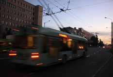 Trolleybus motion blurred. Movement of the trolley along the street at dusk with motion blur stock image